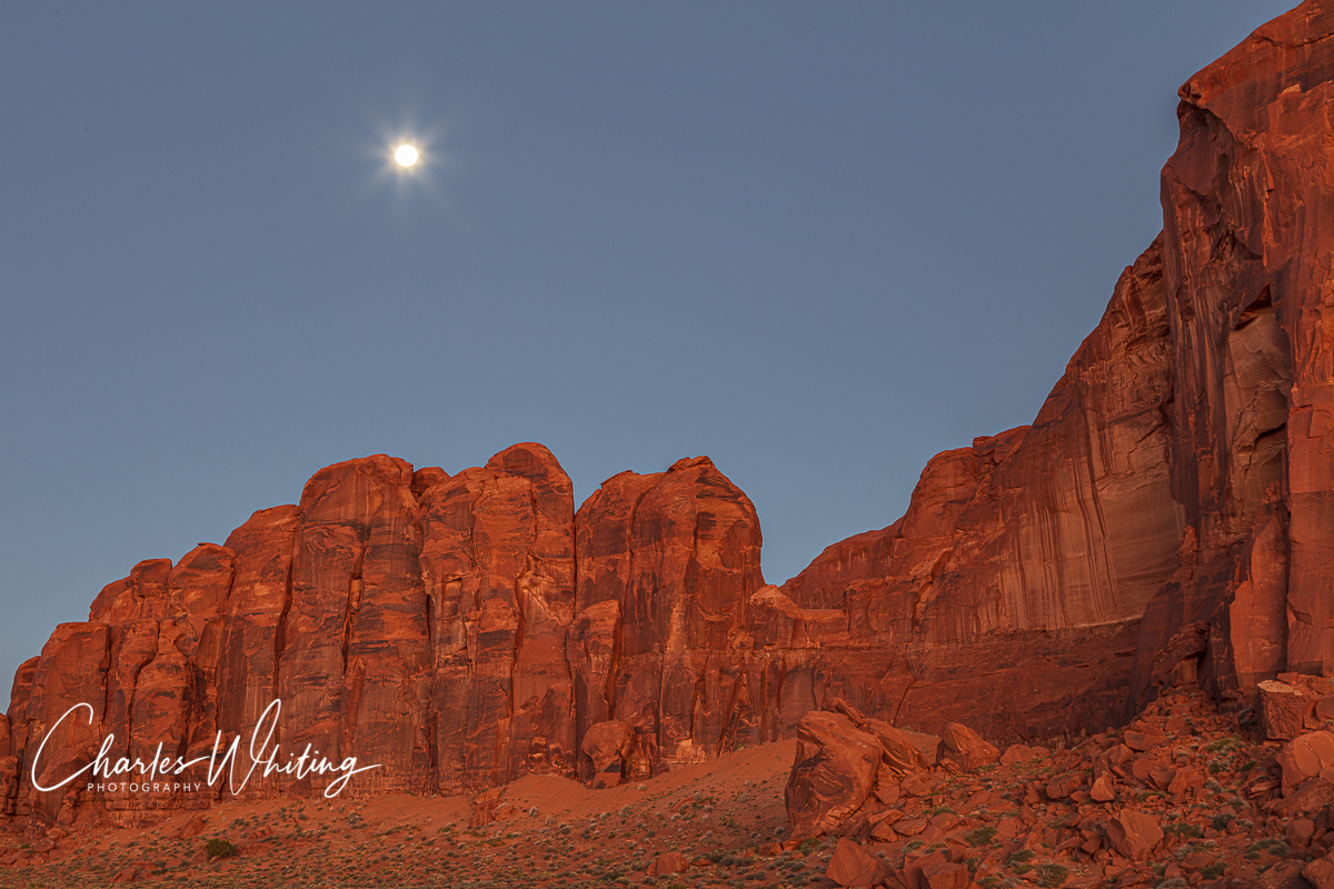 The full moon shines above the red buttes